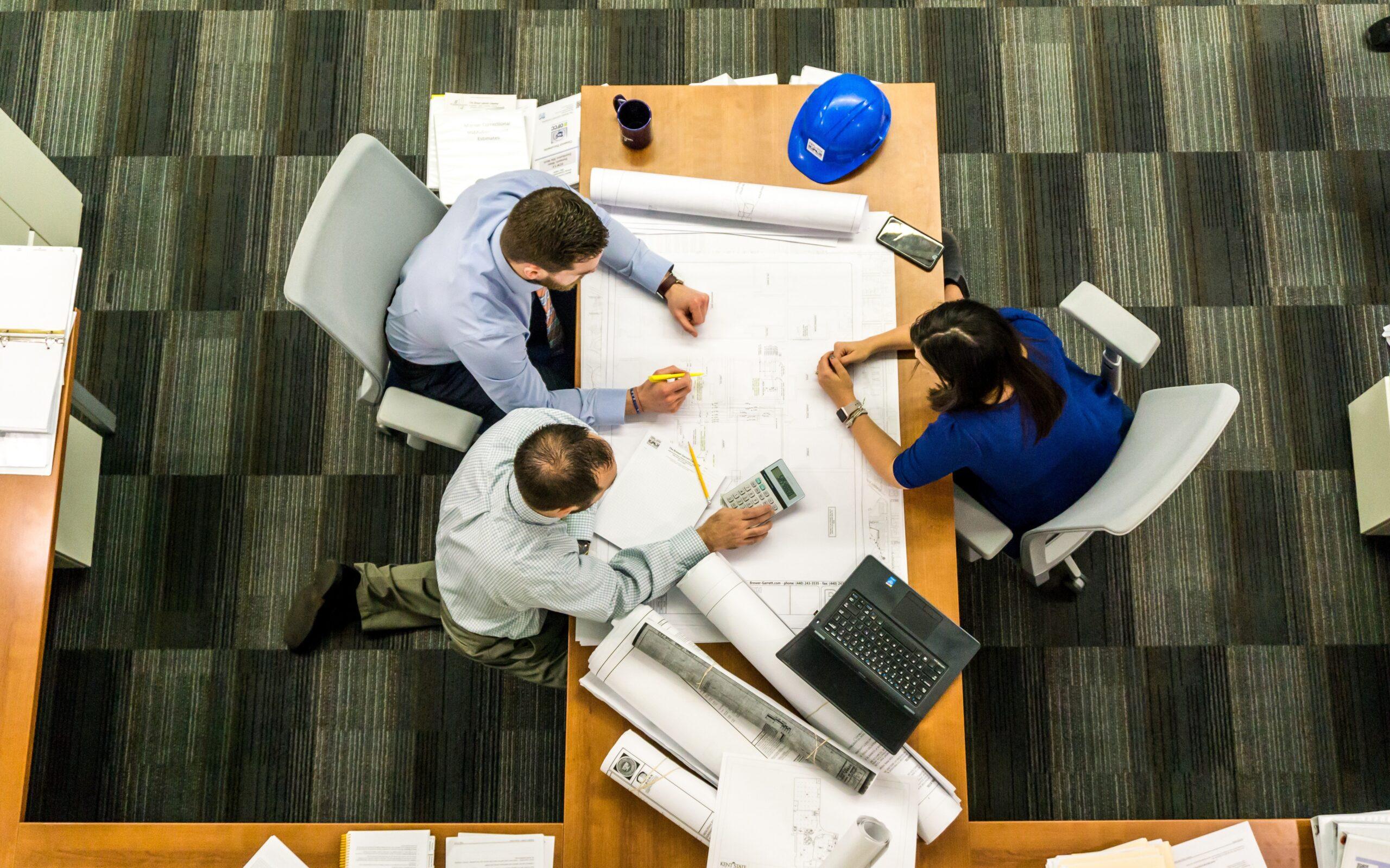 Team sitting around blueprints